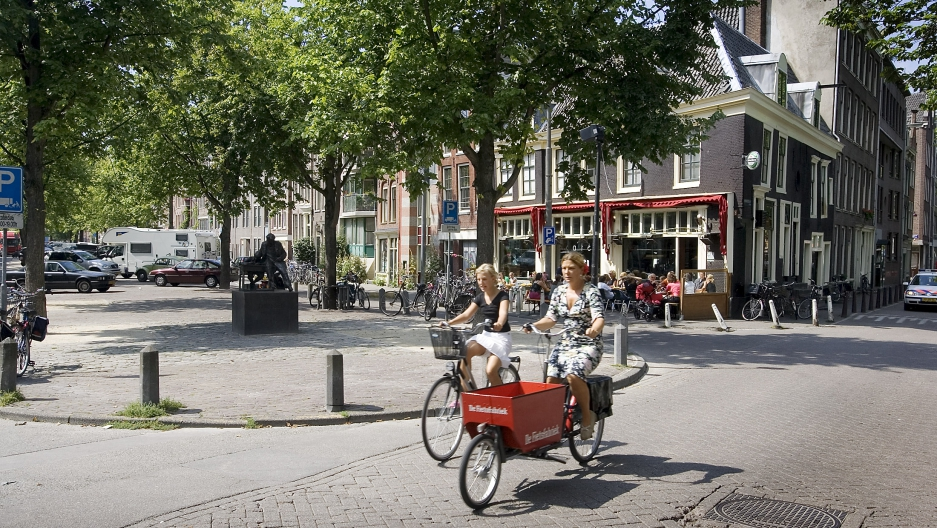 Two women ride their bicycles on the Lindengracht market in Amsterdam in this snapshot dating to August 2004.