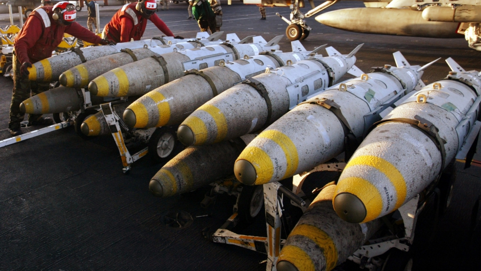 Aviation ordinancemen organize 1000 pound MK-83 JDAM (Joint Direct Attack Munition) bombs on their racks on the flight deck of the USS Kitty Hawk aircraft carrier in this archival photo taken in the northern Persian Gulf March 18, 2003.
