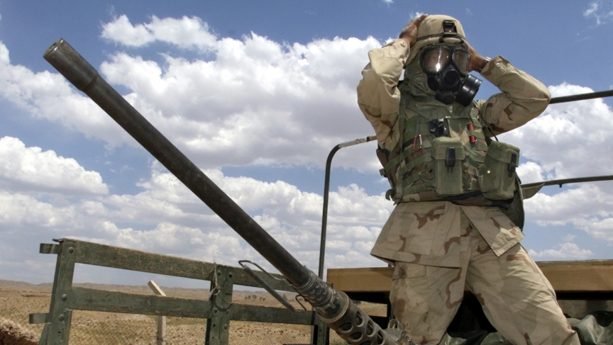 A soldier from the US Army's 173rd Airborne Brigade adjusts his gas mask prior to an air analysis mission near an oil and gas separation plant at the Baba Gurgur oil field outside northern Iraq's town of Kirkuk on May 3, 2003.