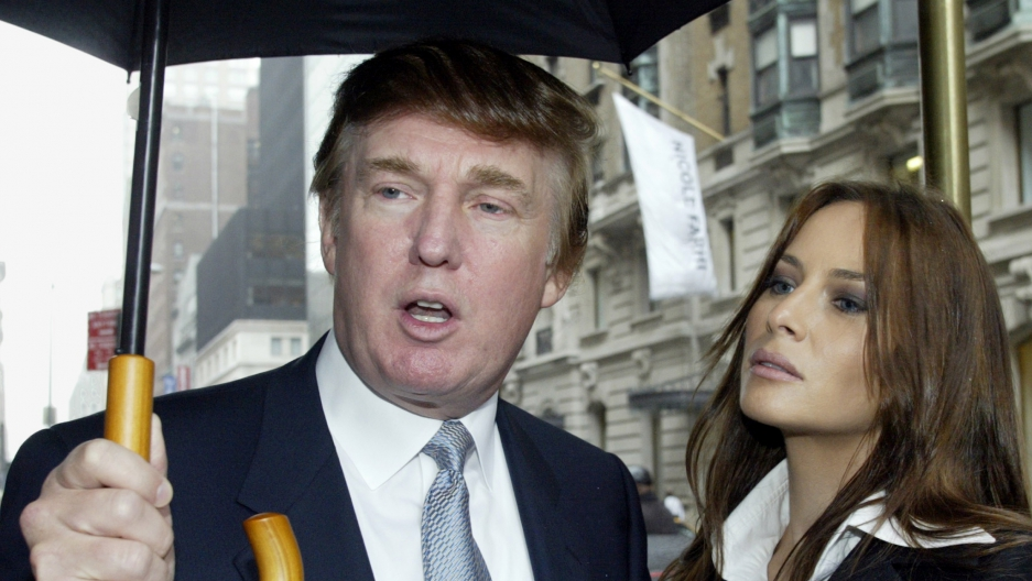 Donald Trump and Melania Trump under an umbrella