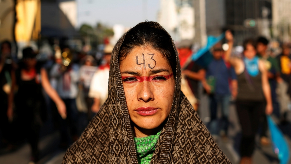 A woman takes part in a march to mark the anniversary of the disappearance of the 43 students of Ayotzinapa College Raul Isidro Burgos a in the state of Guerrero in Mexico City, Mexico February 26, 2017.