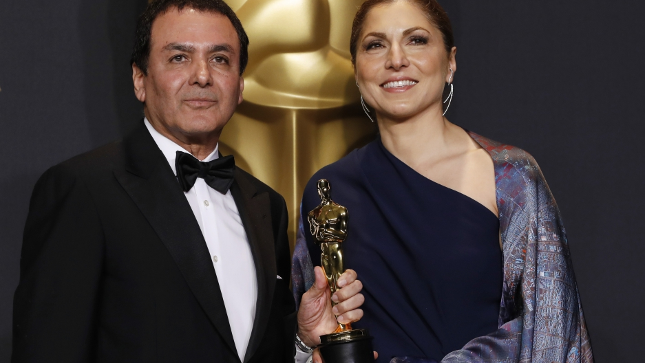 "Anousheh Ansari and Firouz Naderi pose with the Oscar they accepted on behalf of Asghar Farhadi, who won the Best Foreign Language Film for ""The Salesman""."