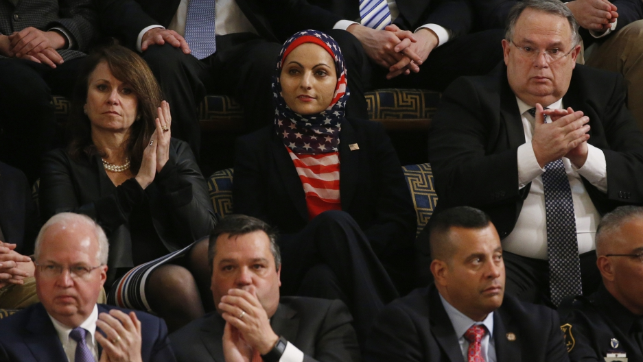 Woman in hijab with American flag pattern amongst men in suits and one woman in black shirt
