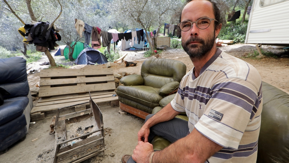 Cedric Herrou, a French farmer and volunteer assisting migrants to cross the French-Italian border to avoid police controls, poses as he sits in a couch near tents for migrants pitched at his land in Breil-sur-Roya, France, April 11, 2017.