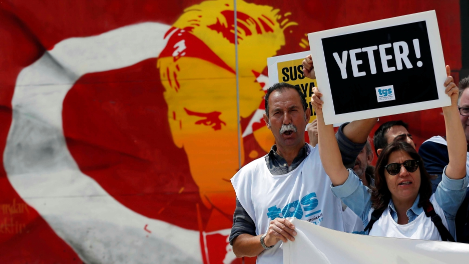 """Members of the Journalists Union of Turkey (TGS) shout slogans during a demonstration to mark World Press Freedom Day in central Istanbul, Turkey, May 3, 2017. The placard reads: """"Enough!"""""""