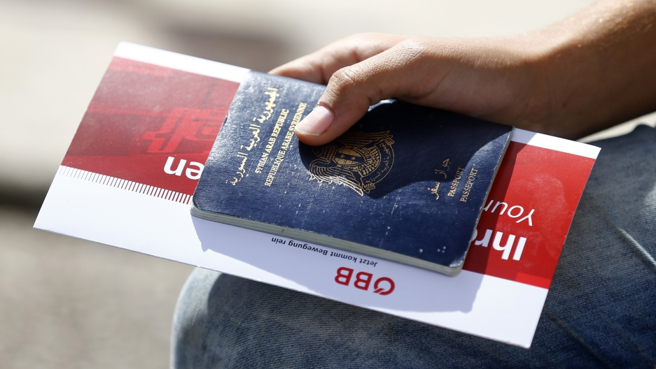 A migrant holds his passport and a train ticket in Freilassing, Germany, September 15, 2015. (Dominic Ebenbichler/Reuters)