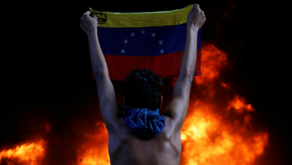 A protester holds a national flag as a bank branch, housed in the Supreme Court of Justice, burns during a rally against Venezuela's President Nicolás Maduro, in Caracas, Venezuela, June 12, 2017.