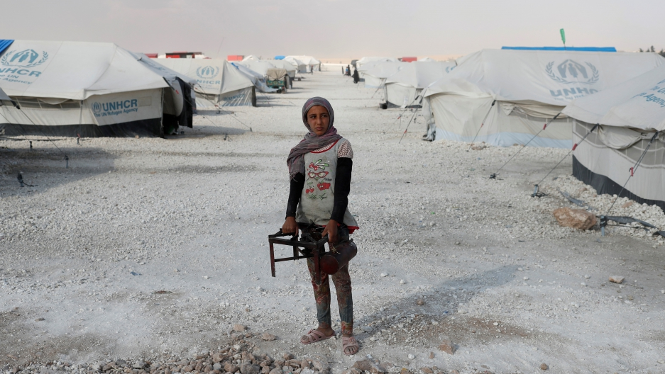 A teenager holds a cooker at a camp for displaced people.