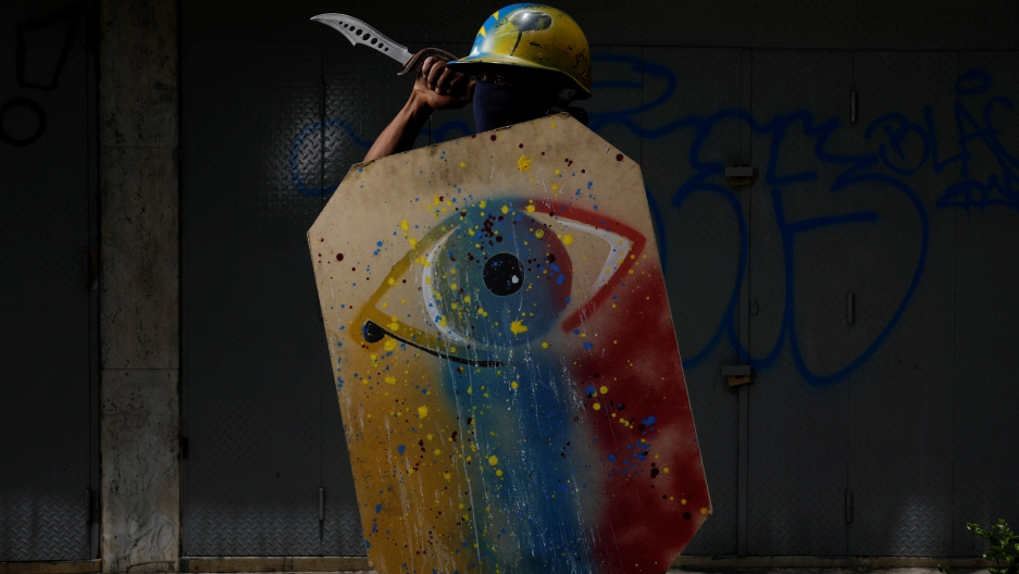 A demonstrator holds a painted shield and a knife.