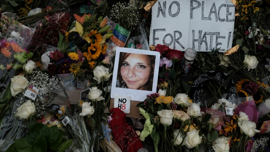 """A photograph of Charlottesville victim Heather Heyer is seen amongst flowers left at the scene of the car attack on a group of counter-protesters that took her life during the """"Unite the Right"""" rally in Charlottesville, Virginia, August 14, 2017."""