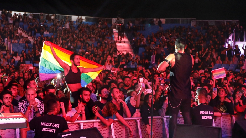 A fan of  Mashrou' Leila holds a rainbow flag during their concert