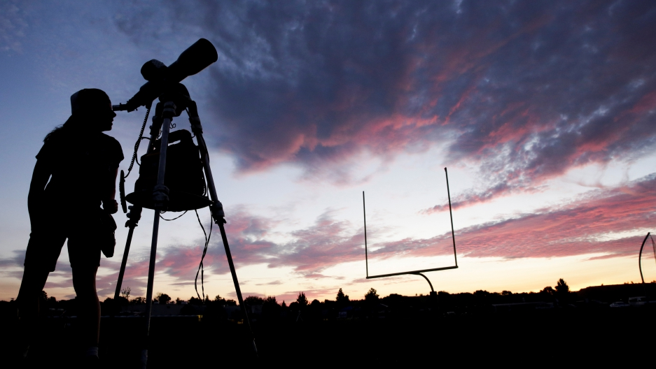 A woman looks through a telescope on the football field at Madras High School the evening before a solar eclipse in Madras, Oregon, Aug. 20, 2017.