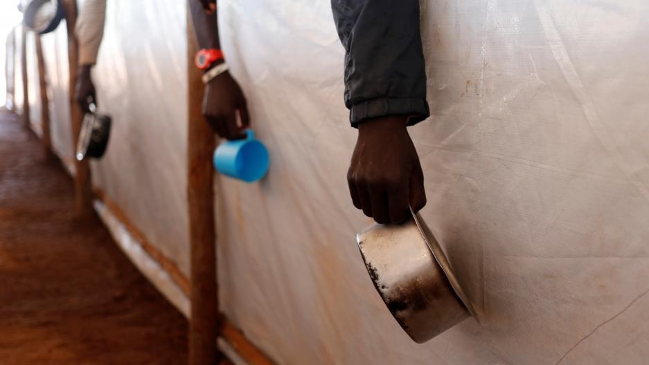South Sudanese refugees wait in line for food in Omugo refugee settlement camp in northern Uganda