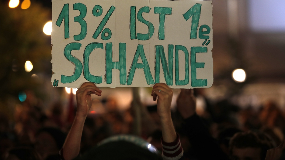 "A demonstrator holds a poster reading ""13 percent is a shame"" during a protest against the anti-immigration party Alternative fuer Deutschland (AfD) after German general election in Berlin."