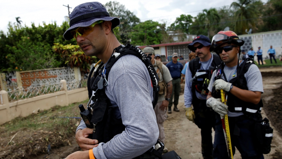 """Members of the Federal Emergency Management Agency (FEMA) """"Urban Search and Rescue"""" team conduct a search operation in an area hit by Hurricane Maria in Yauco, Puerto Rico on September 25, 2017."""