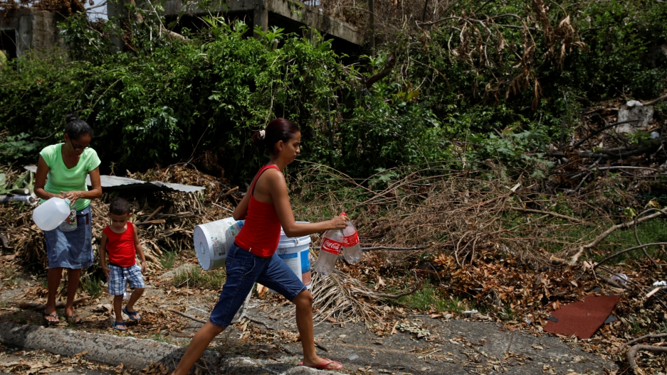 People carry containers that will be filled with water from a tank truck at an area hit by Hurricane Maria in Canovanas, Puerto Rico, Sept. 26, 2017.