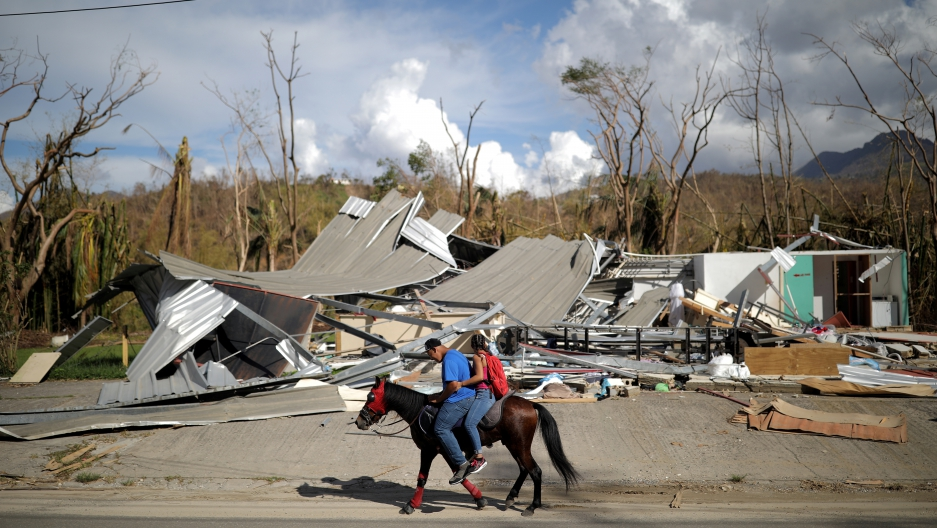 Local residents ride a horse by a destroyed building after Hurricane Maria in Jayuya, Puerto Rico