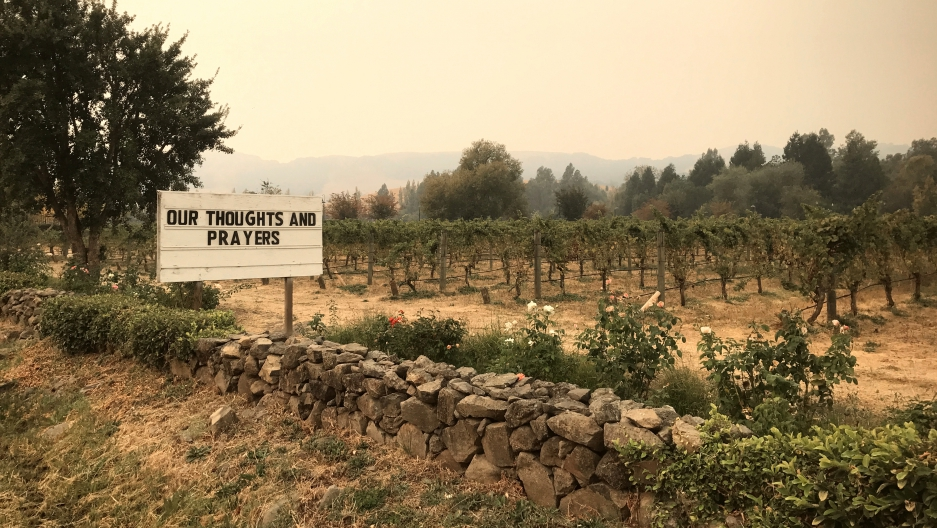 A sign outside the Cline Cellars vineyards as smoke from various wildfires fills in the distance