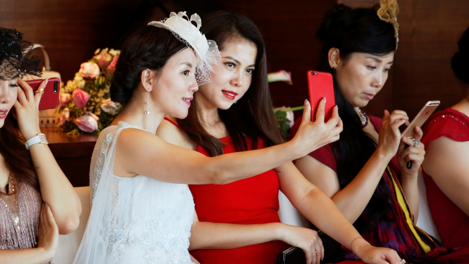 Participants take a selfie during an etiquette class by former Australian model June Dally-Watkins in Guangzhou, China October 8, 2017.