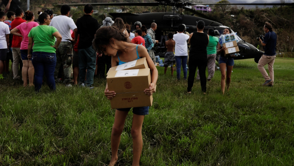 A young girl looks back after getting her shoe stuck in the mud while carrying supplies
