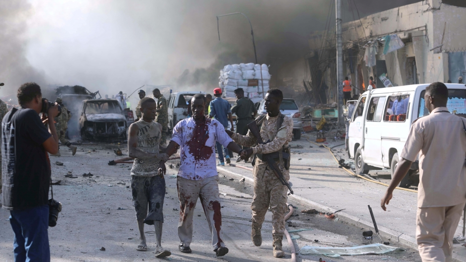 A Somali government soldier evacuates an injured man from the scene of an explosion.