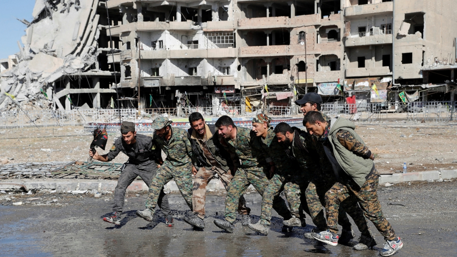 Syrian Democratic Forces fighters dance along a street in Raqqa, Syria, on Oct. 18, 2017.
