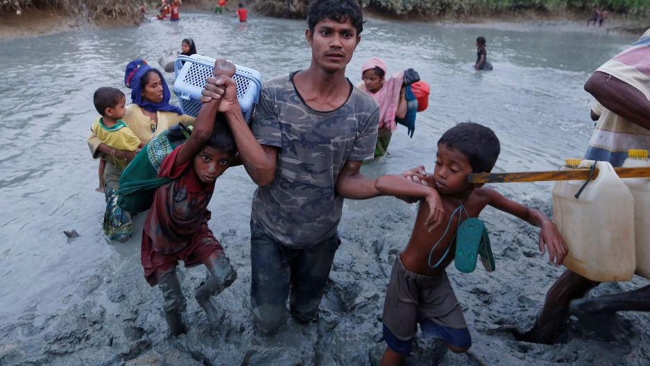 A Rohingya refugee helps children cross the mud after crossing the Naf River at the Bangladesh-Myanmar border.