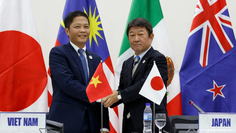 Japan's Minister of Economic Revitalization Toshimitsu Motegi, right, and Vietnam's Industry and Trade Minister Tran Tuan Anh shake hands after they attended a news conference on the Trans Pacific Partnership (TPP) Ministerial Meeting during APEC 2017 in