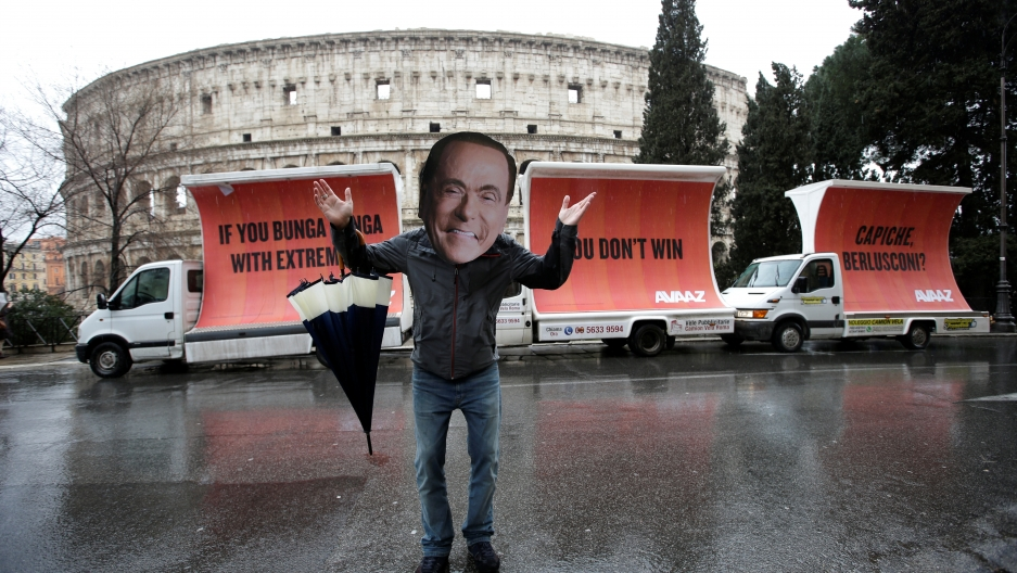 An activist wearing a mask of Forza Italia party leader Silvio Berlusconi poses during a tour, the day after Italy's parliamentary elections, in Rome, Italy March 5, 2018.