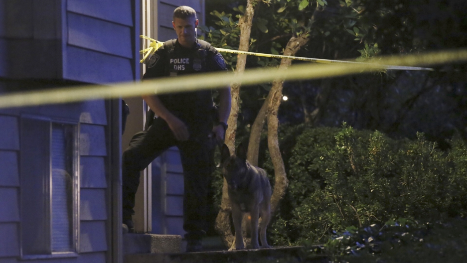 A DHS police investigator is seen with a canine at residential location following a mass shooting at Umpqua Community College in Roseburg, Oregon October 1, 2015.