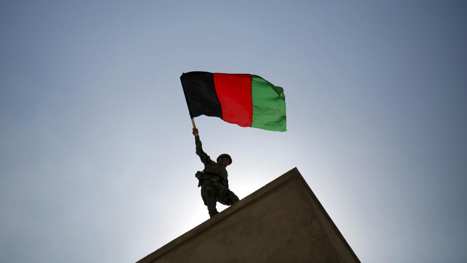 An Afghan National Army officer holds an Afghanistan flag during a training exercise at the Kabul Military Training Centre in Afghanistan, Oct. 7, 2015.