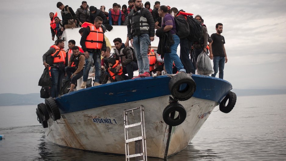 Migrants and refugees are seen aboard a Turkish fishing boat as they arrive on the Greek island of Lesbos after crossing a part of the Aegean Sea from theTurkish coast to Lesbos.