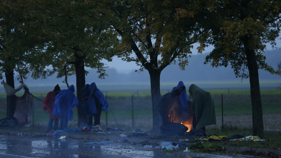 Migrants warm themselves next to a fire as they wait to cross the border from Croatia into Slovenia.