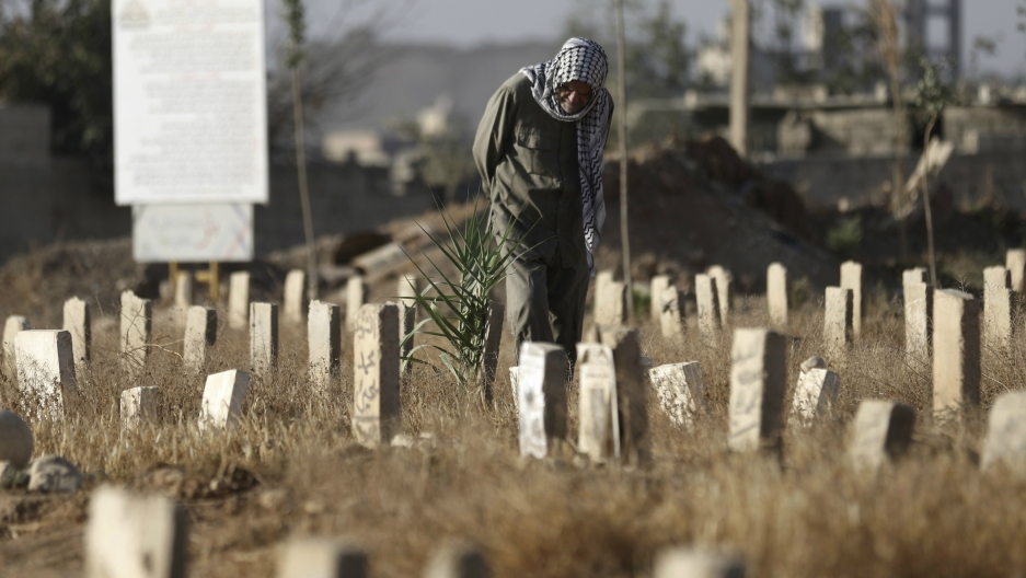 A man visits a cemetery on the first day of Eid al-Adha in Douma, near Damascus, Syria, Sept. 24, 2015.