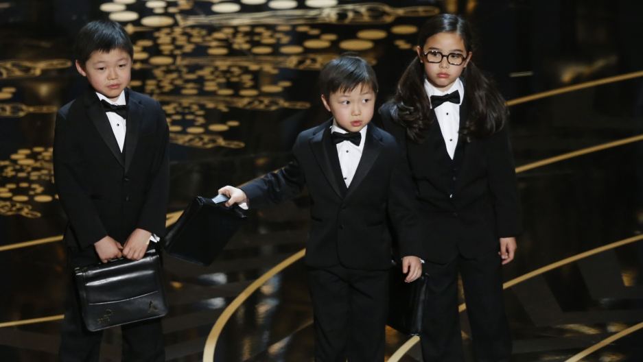 Three children in tuxedos on stage at the Oscars