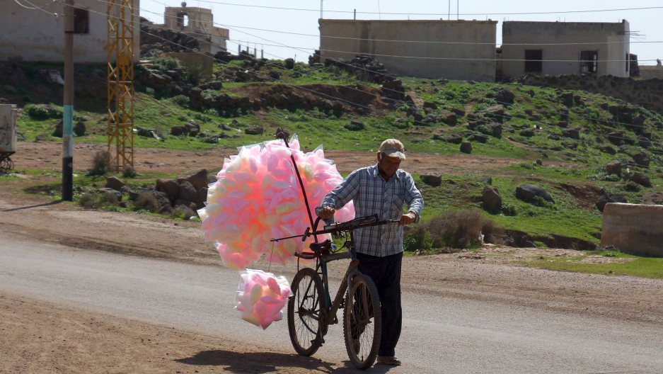 A man sells cotton candy as he pushes his bicycle along a street in the rebel held al-Ghariyah al-Gharbiyah town, in Deraa province.