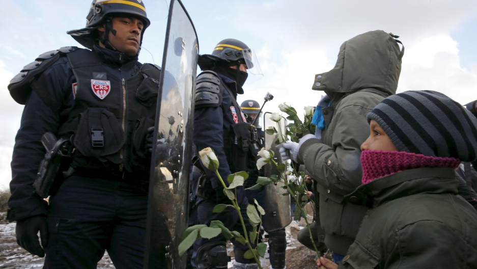 """Youngs migrants holding white flowers face French riot police officers who secure the area near makeshift shelters during the partial dismantlement of the camp for migrants called the """"Jungle"""" in Calais, France, March 7, 2016."""