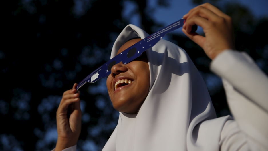 A school girl watches a partial solar eclipse at the Planetarium in Kuala Lumpur, Malaysia, March 9, 2016.