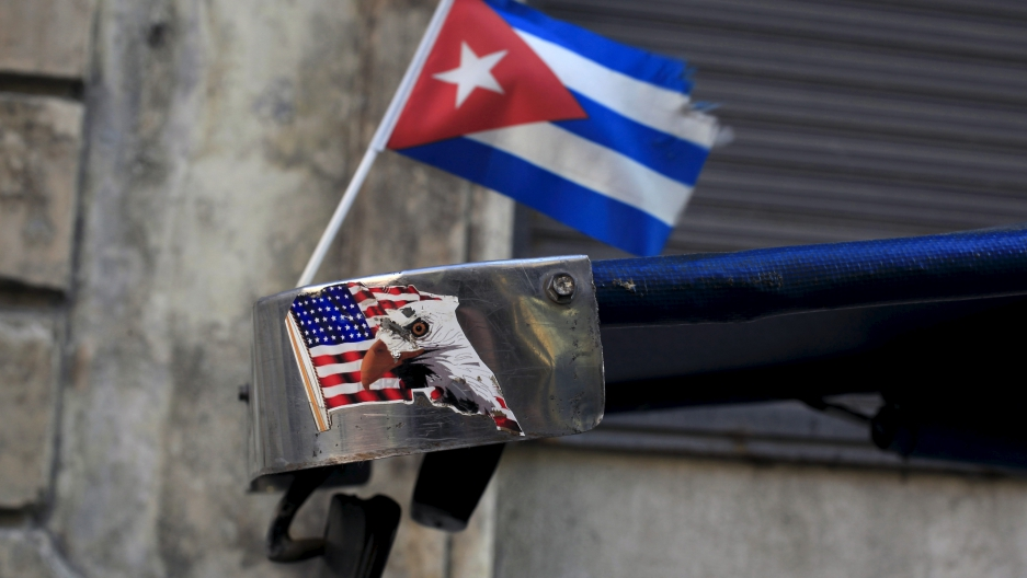 A Cuban flag and a sticker of a U.S. flag are seen on the roof of tricycle taxi in Havana March 9, 2016.