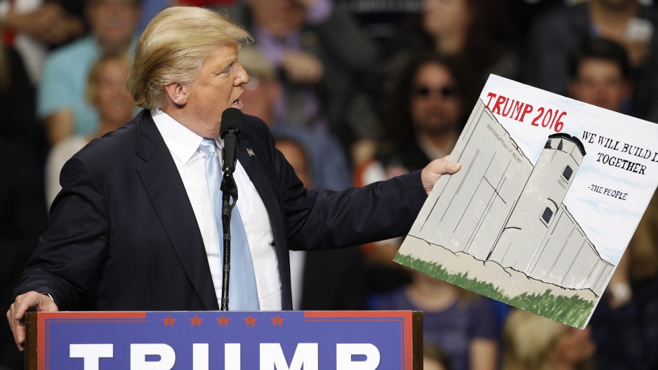 Donald Trump holds a sign supporting his plan to build a wall
