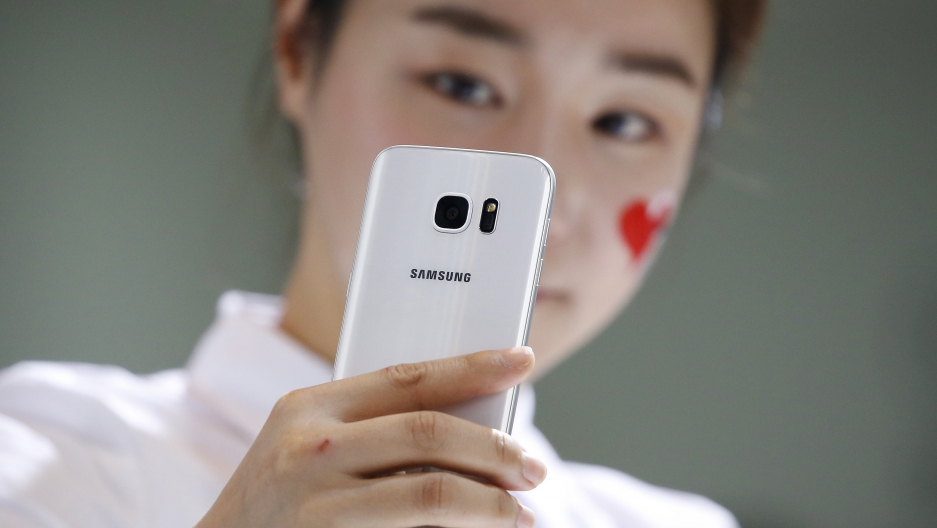 A model demonstrates a Samsung Electronics' new smartphone Galaxy S7 during its launching ceremony.