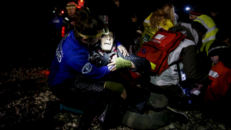Rescuers try to revive an unconscious refugee who arrived on a dinghy on the Greek island of Lesbos. Two unconscious arrivals were taken to a hospital and were later pronounced dead.