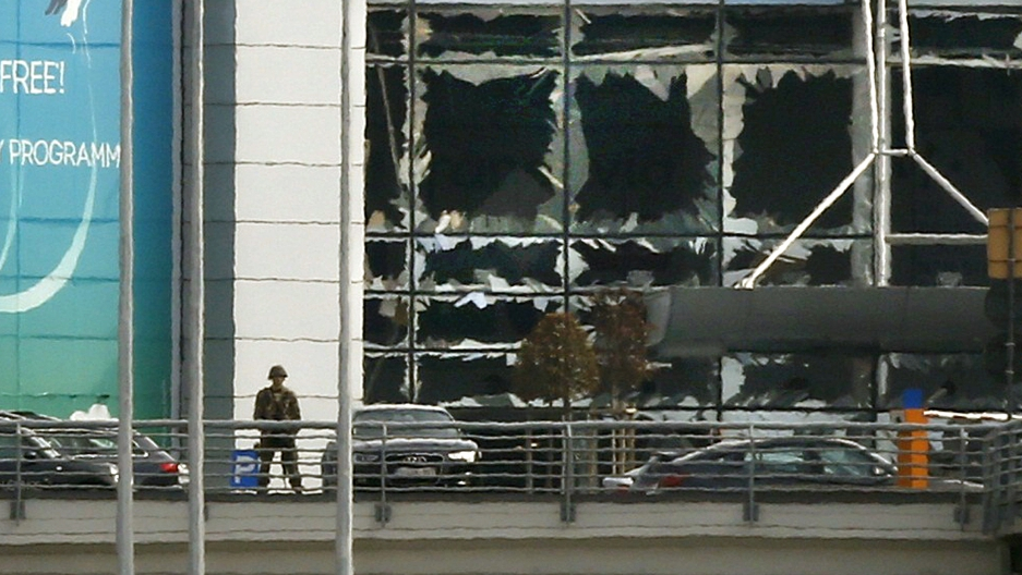 A soldier stands near broken windows after explosions at Zaventem airport near Brussels