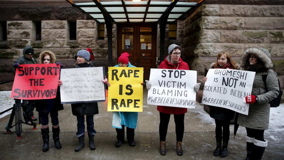 Protesters stand outside of the courthouse before an Ontario judge found former Canadian radio host Jian Ghomeshi not guilty on four sexual assault charges and one count of choking.