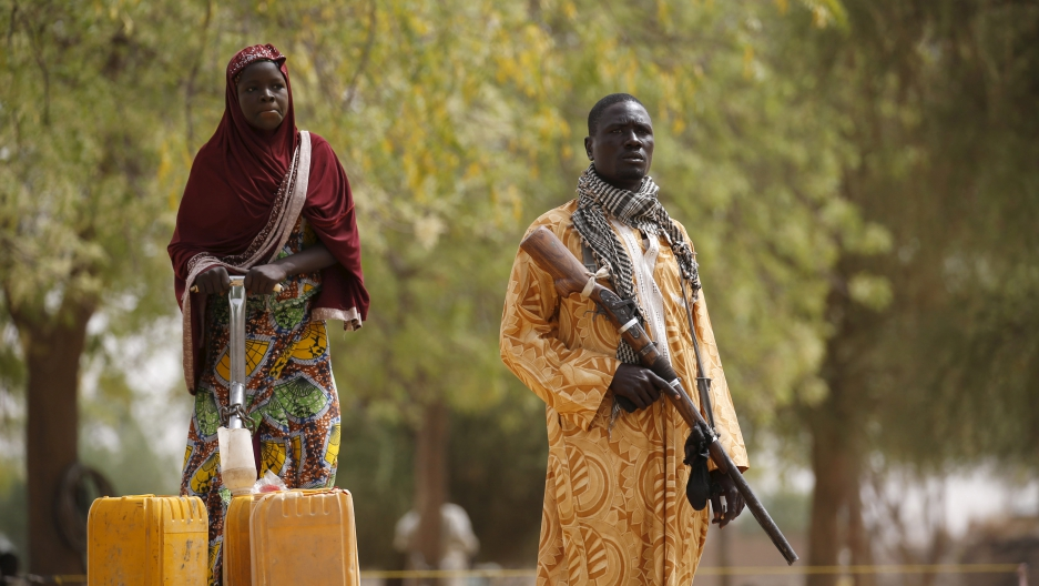 A member of a civilian vigilante group holds a hunting rifle while a woman pumps water into jerrycans in Kerawa, Cameroon, March 16, 2016.