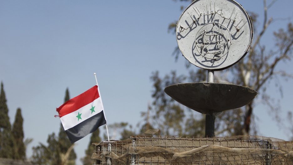 A Syrian national flag flutters next to the Islamic State's slogan at a roundabout where executions were carried out by ISIS militants in the city of Palmyra, in Homs Governorate, Syria April 1, 2016.