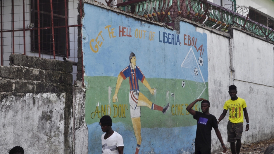 "Men walk by a mural that reads ""Get the hell of Liberia, Ebola! And don't come back"" in Monrovia, Liberia, April 1, 2016."