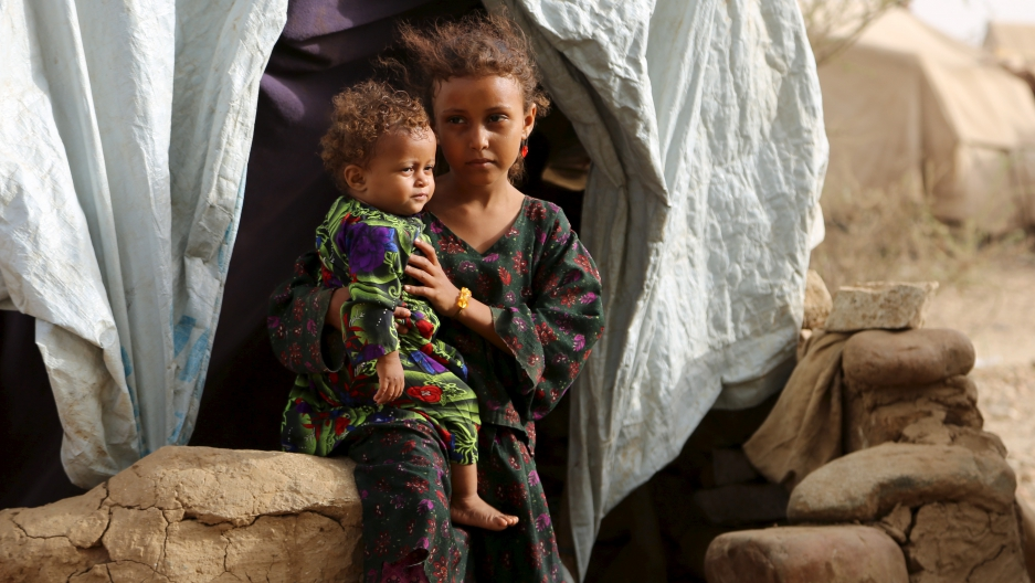 A girl holds her sister outside their family's hut at the Shawqaba camp for internally displaced people who were forced to leave their villages by the war in Yemen's northwestern province of Hajjah March 12, 2016
