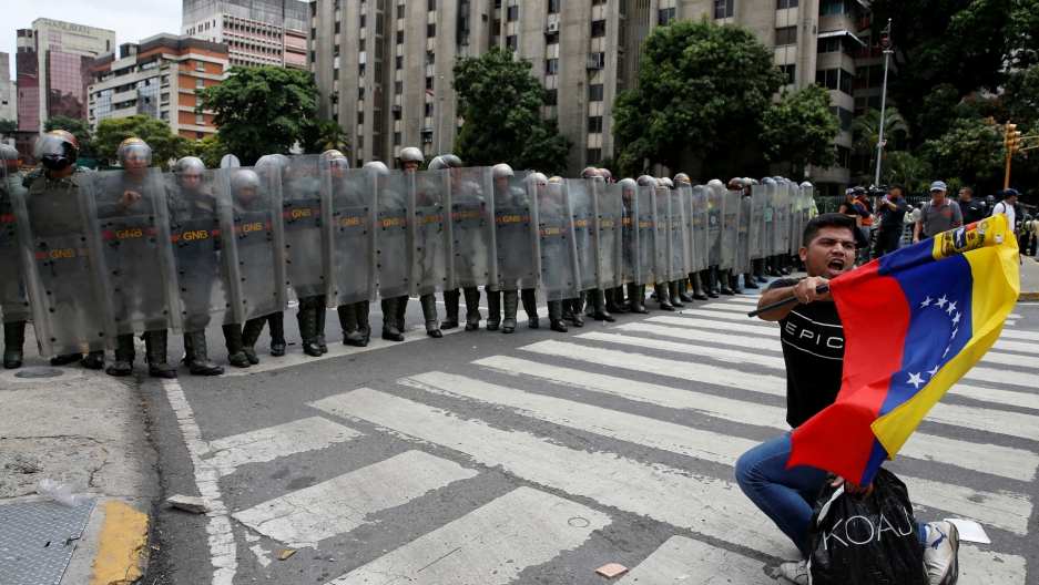An opposition supporter carrying a Venezuelan flag kneels in front of National Guards during a rally to demand a referendum to remove President Nicolas Maduro in Caracas, Venezuela, May 18, 2016.