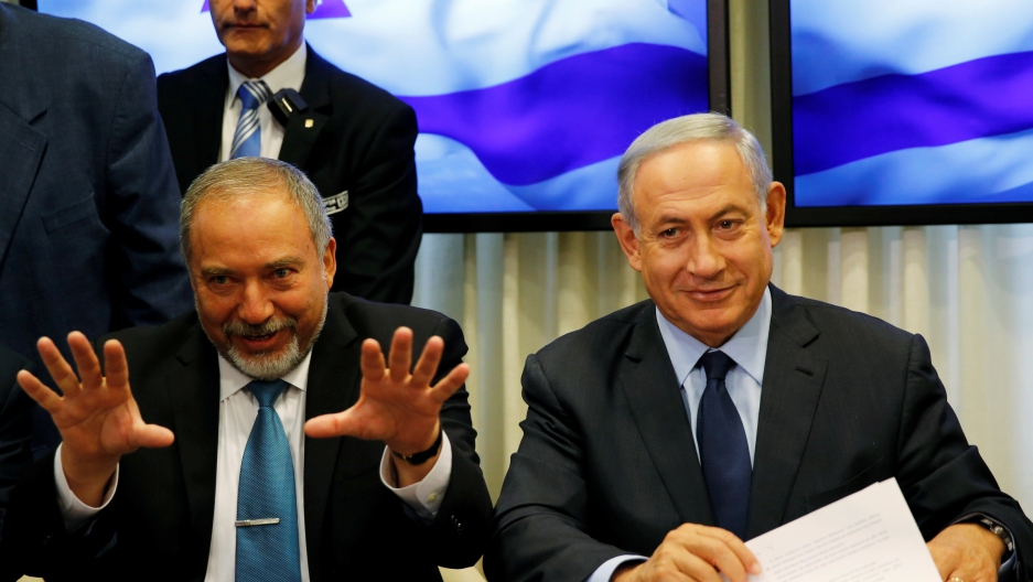 Israel's new defense minister, Avigdor Lieberman, left, next to Israeli Prime Minister Benjamin Netanyahu as they sign a coalition deal to broaden the government's parliamentary majority on May 25.